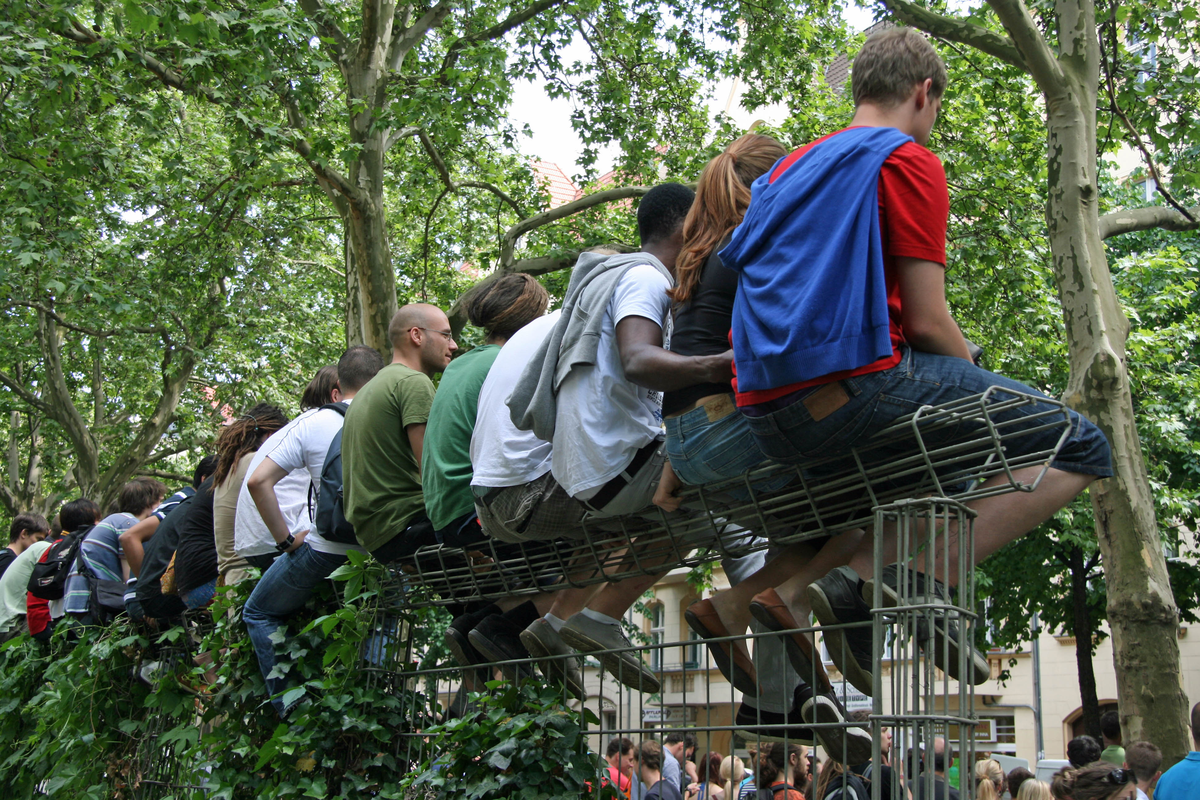 Carnival goers climb a trellis for a better view of the parade at Karneval der Kulturen (Carnival of Cultures) in Berlin