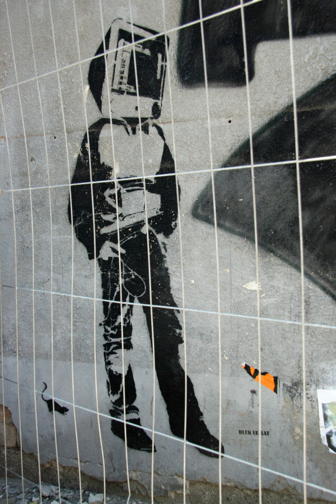 Monitor Head: Street Art by Blek le Rat behind the bars of a fence in Berlin