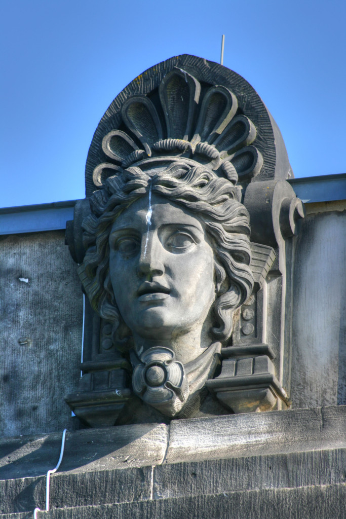 A carved figurehead in the stonework around the roof of the Reichstag in Berlin