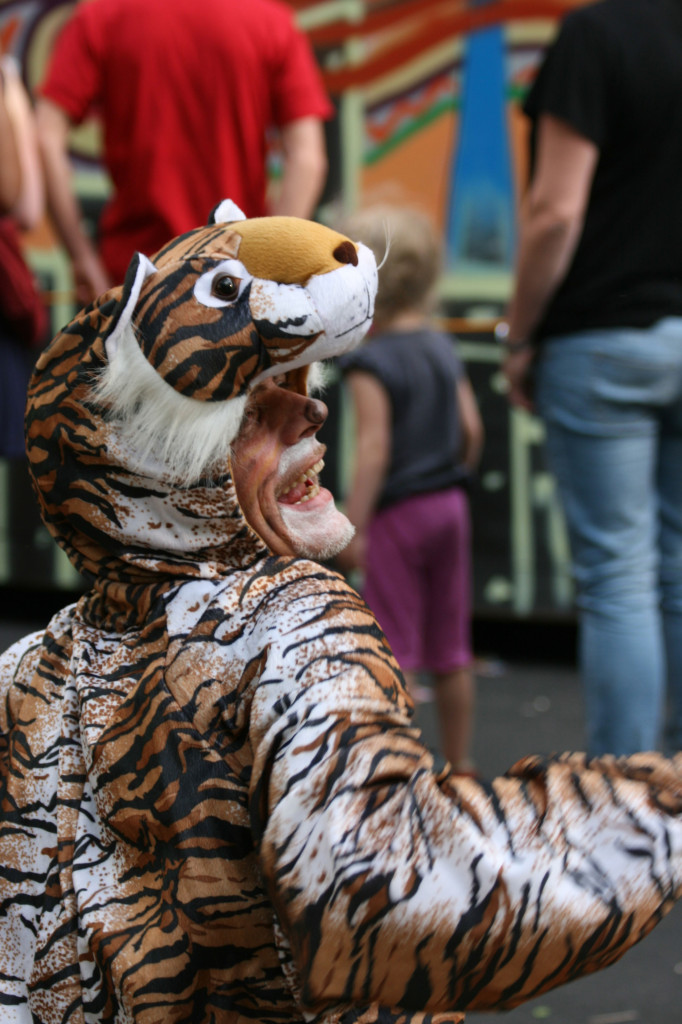 A man in a Tiger costume watches the parade at at Karneval der Kulturen (Carnival of Cultures) in Berlin
