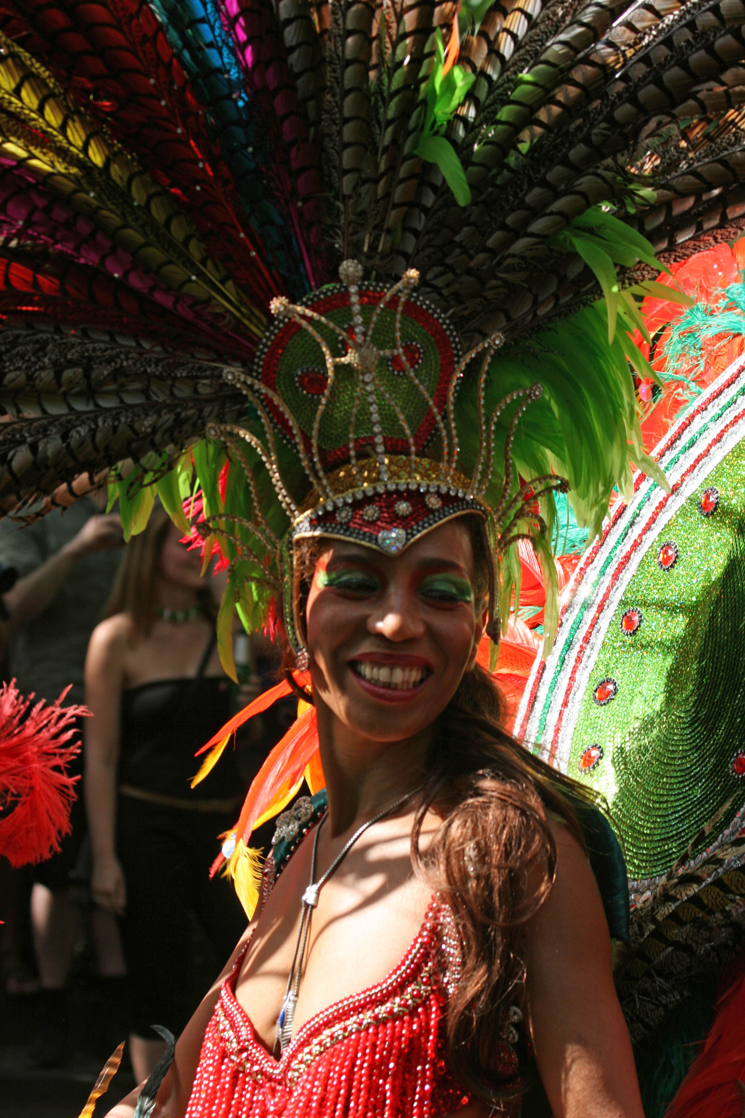 A lady in a feathered headdress dances at Karneval der Kulturen (Carnival of Cultures) in Berlin