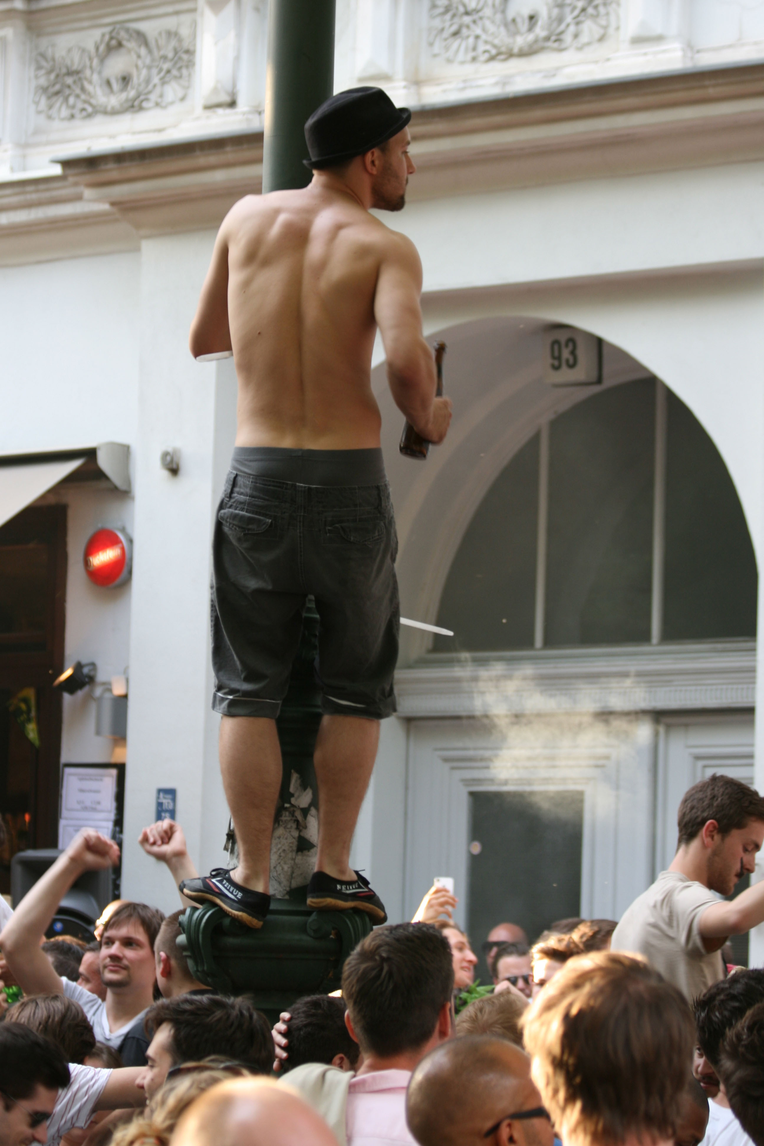A man climbs a Lamp Post for a better view at Karneval der Kulturen (Carnival of Cultures) in Berlin