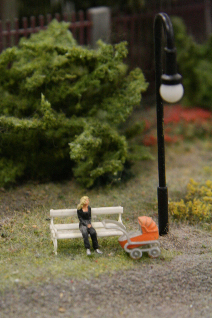 A mum takes a break on a park bench with her pram at Loxx Miniatur Welten Berlin