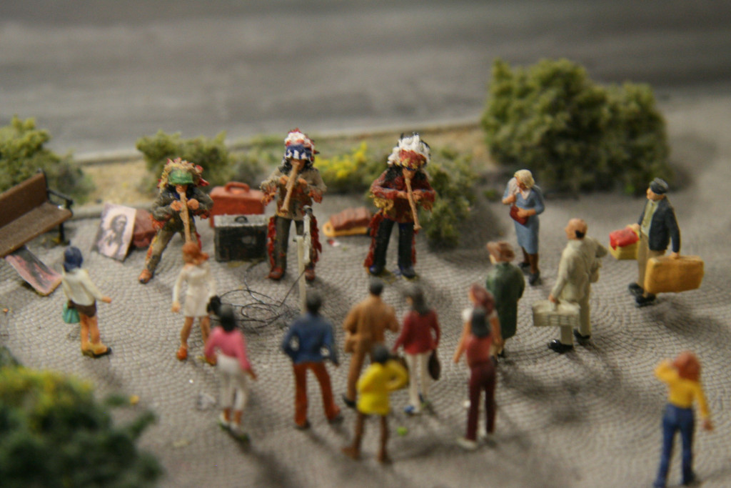 Street musicians in Native Indian dress perform to a crowd at Loxx Miniatur Welten Berlin