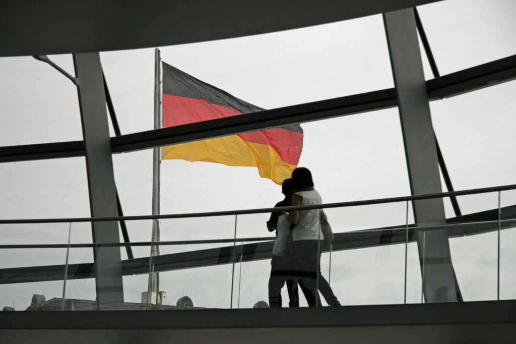 Tourists passing the German flag as they climb the dome of the Reichstag in Berlin