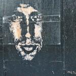 Street Art by Vhils on a wooden hoarding in Camden