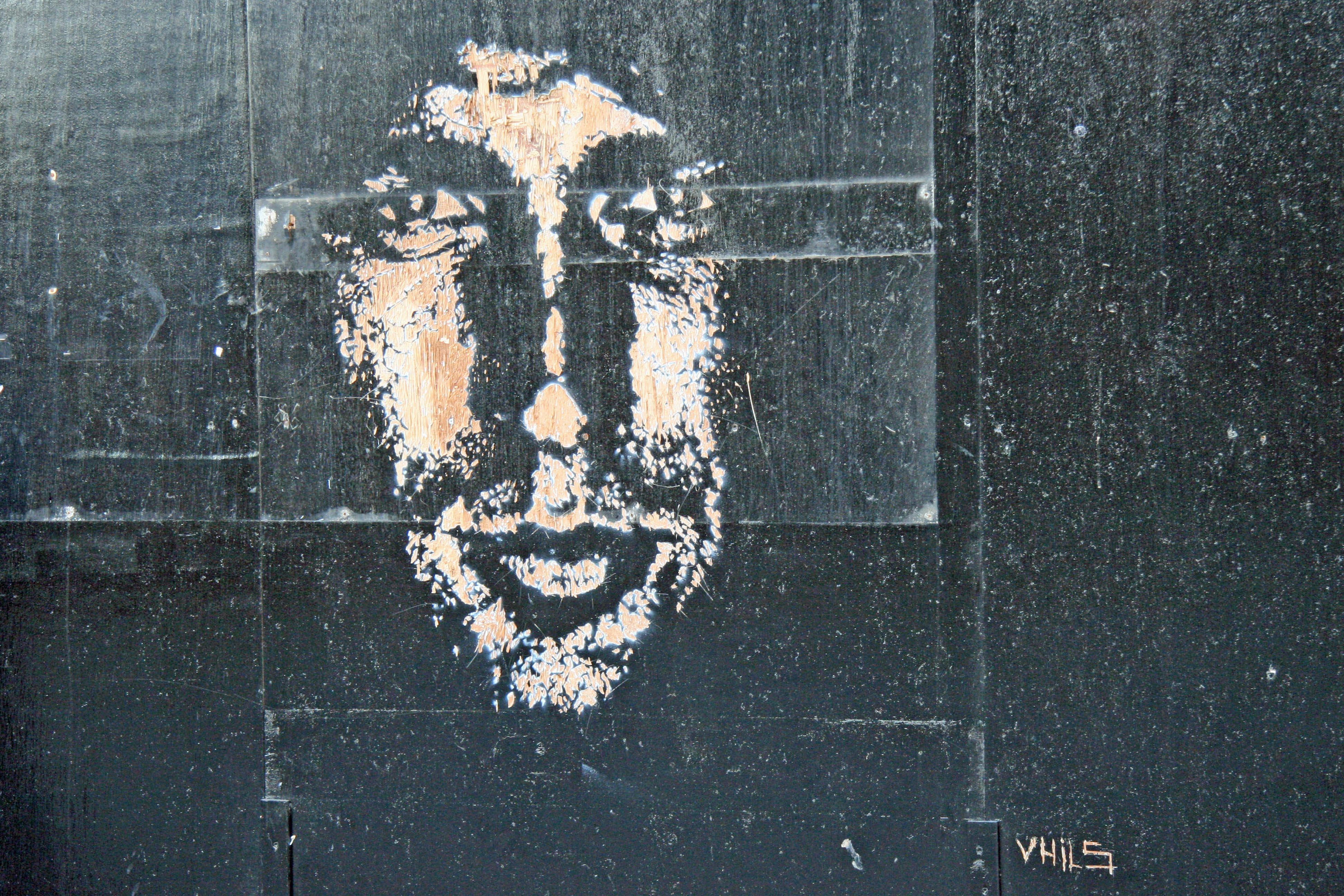 Street Art by Vhils on a wooden hoarding in Camden