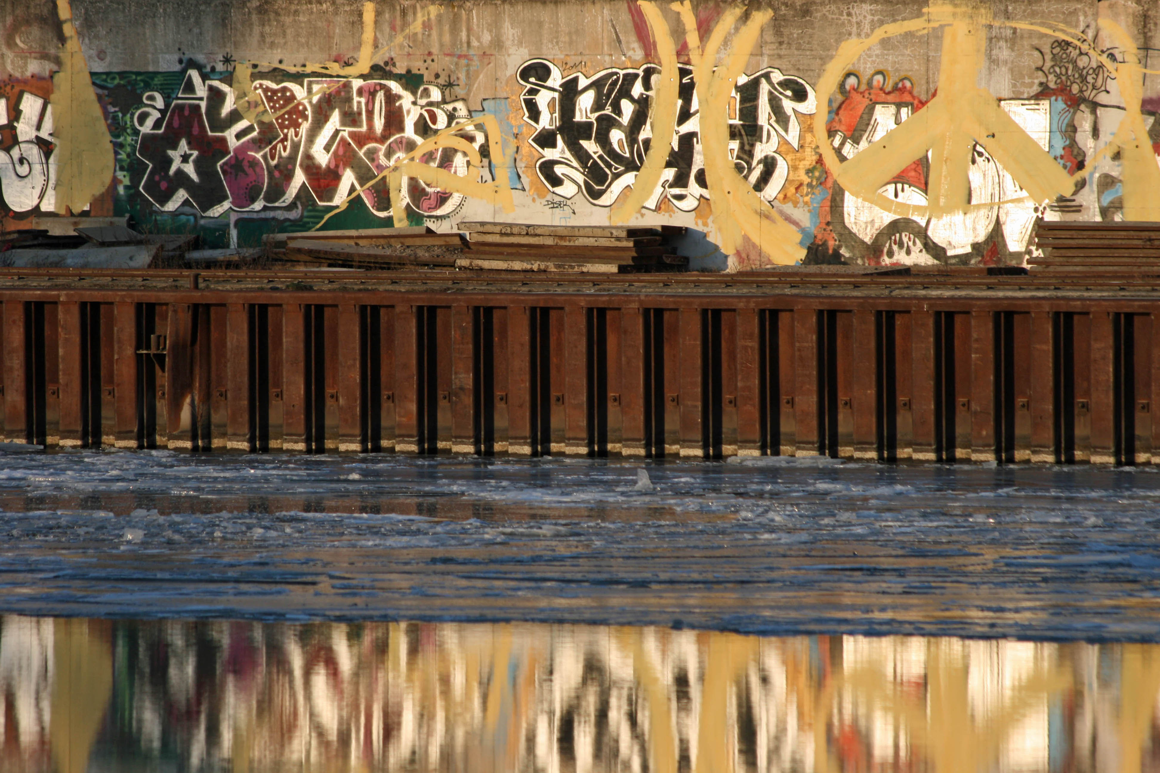 Graffiti on the bank of the partially frozen Spree in a Berlin Winter
