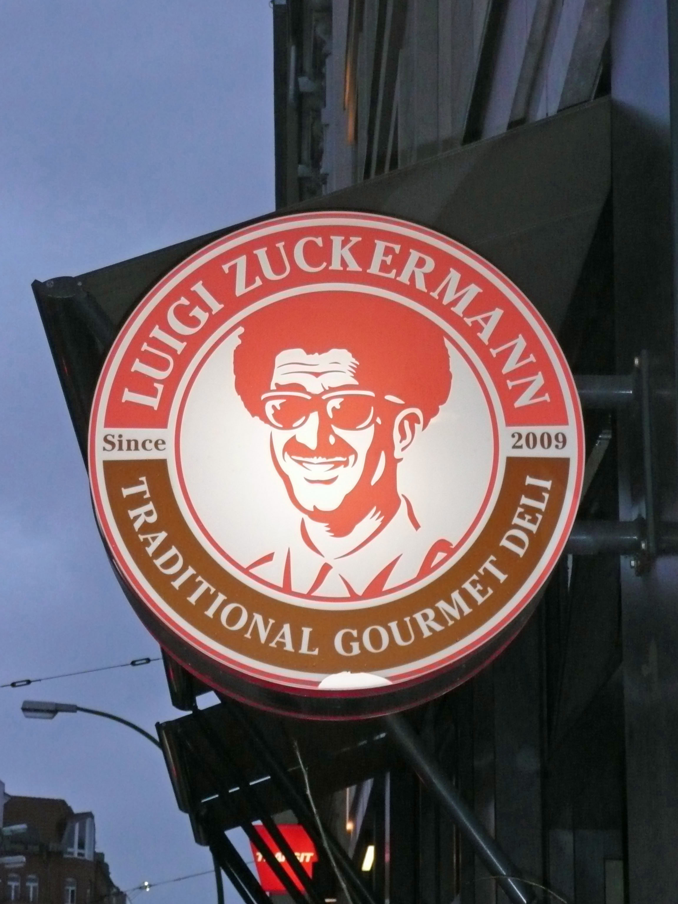 The sign for Luigi Zuckermann, a deli in Berlin, lit up at dusk
