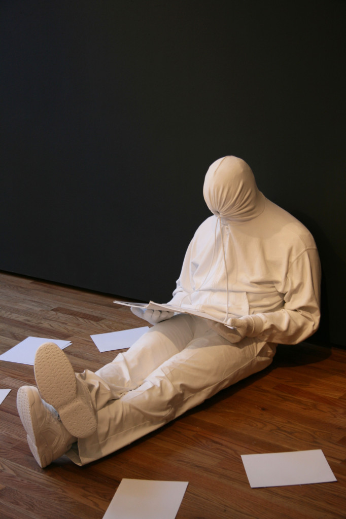 A man sits on the floor reading - a sculpture by Mark Jenkins, part of the Glazed Paradise exhibition at Gestalten in Berlin