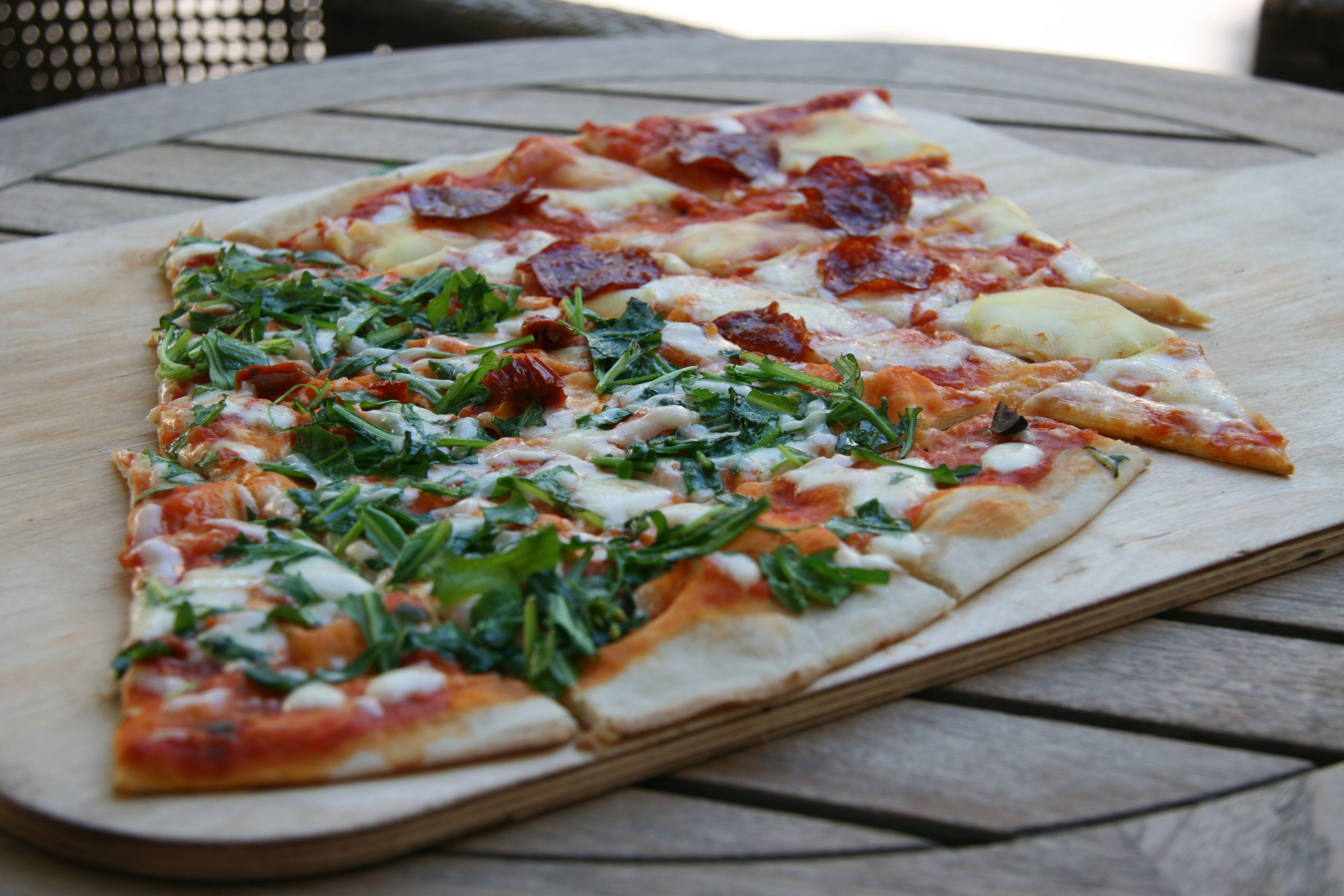Slices of Spicy Salami and Ruccola (Rocket) pizza at Caramello in Prenzlauer Berg, Berlin