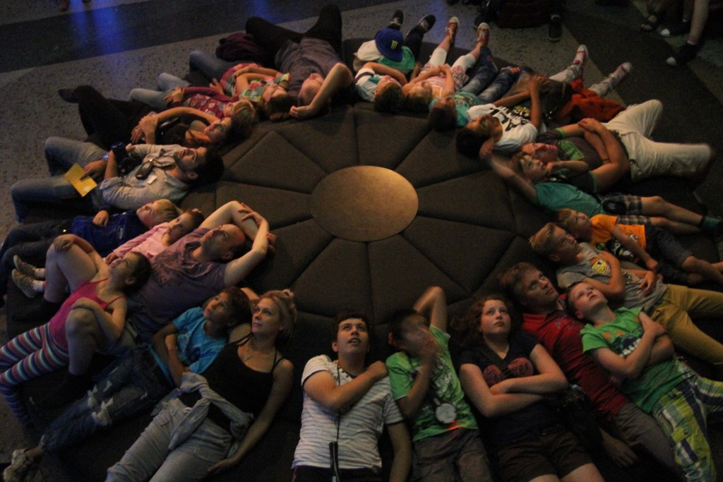 Visitors on a round sofa viewing the multimedia installation in the Cosmos and Solar System exhibition at the Museum für Naturkunde (Natural History Museum) in Berlin