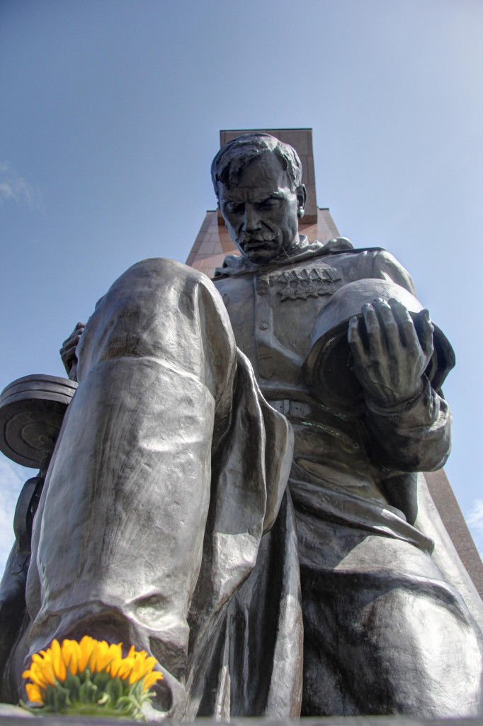 A close up from below of a statue of a kneeling soldier at the Soviet War Memorial in Teptower Park in Berlin