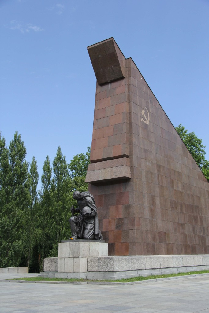 The red granite and a statue of a kneeling soldier at the Soviet War Memorial in Teptower Park in Berlin