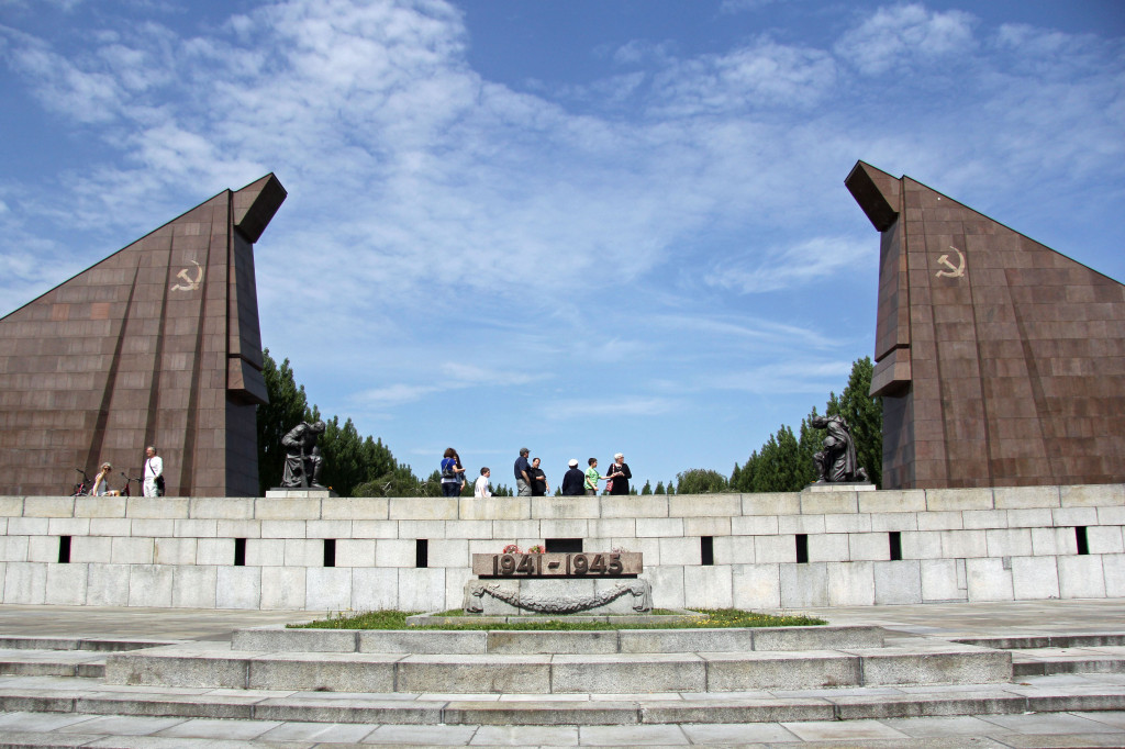 The red granite gateway and statues of kneeling soldiers at the Soviet War Memorial in Teptower Park in Berlin