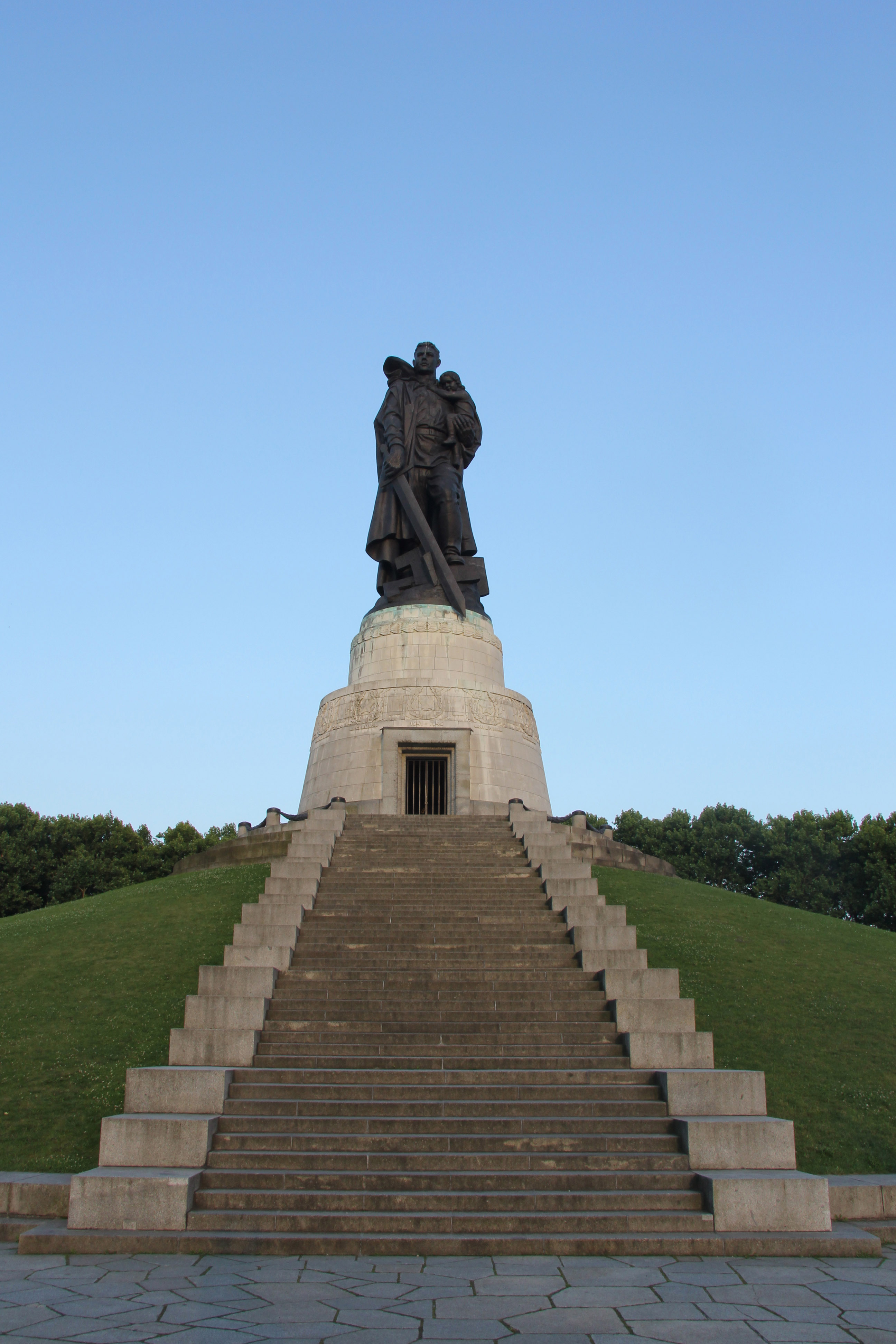 The statue of a Soviet soldier carrying a German child and crushing a Swastika beneath his boot at the Soviet War Memorial in Treptower Park in Berlin