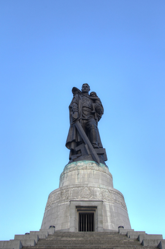 The statue of a Soviet soldier carrying a German child and crushing a Swastika beneath his boot from the steps at the Soviet War Memorial in Treptower Park in Berlin