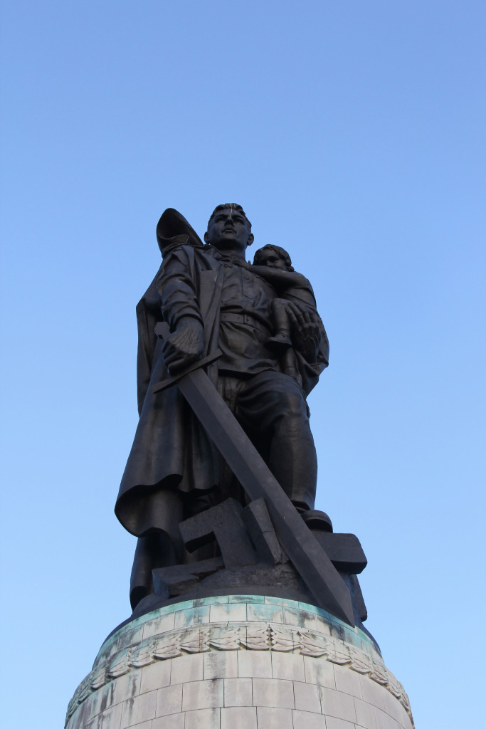 A close up of the statue of a Soviet soldier carrying a German child and crushing a Swastika beneath his boot at the Soviet War Memorial in Treptower Park in Berlin