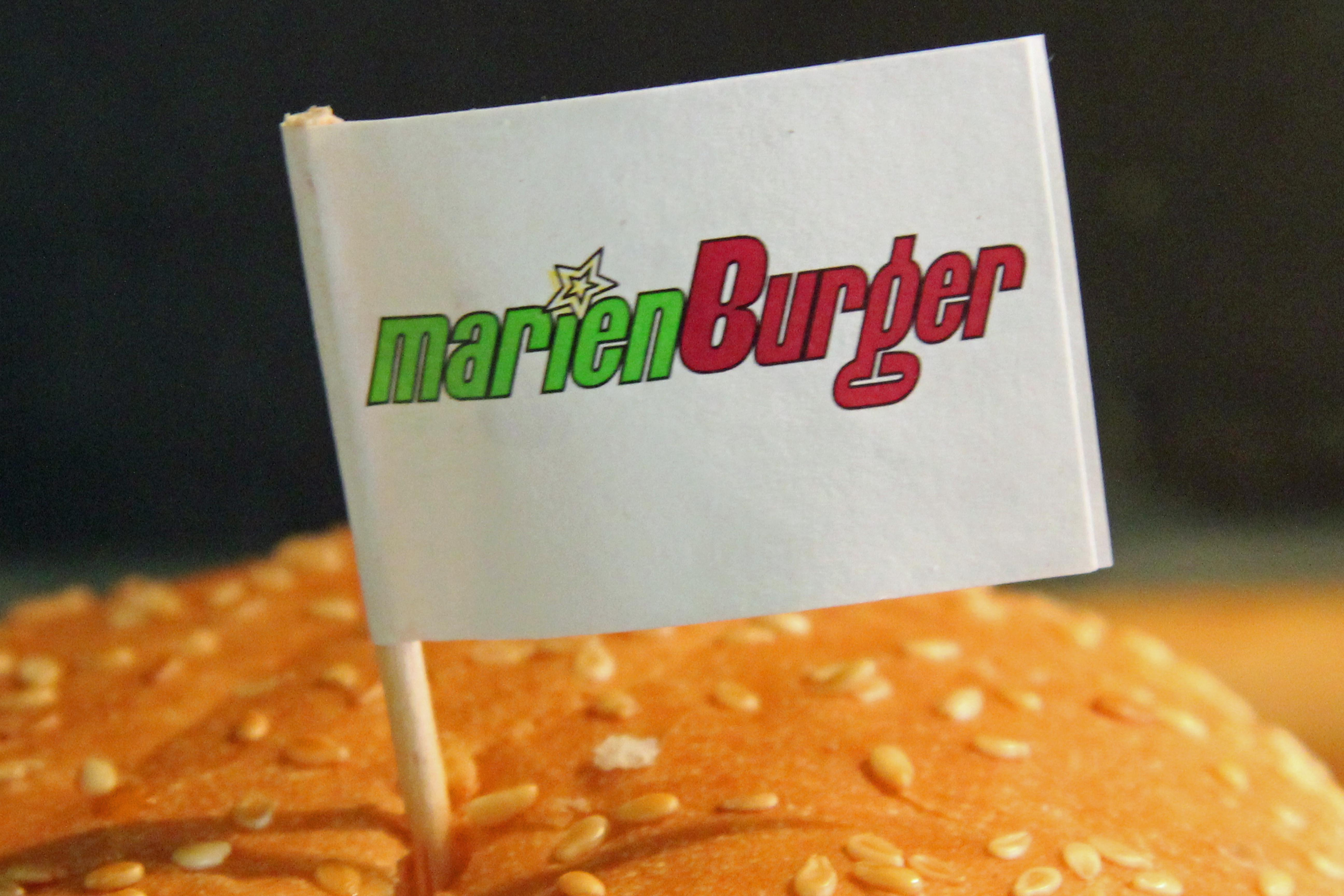 The Marienburger logo on a flag stuck in the burger bun in Berlin