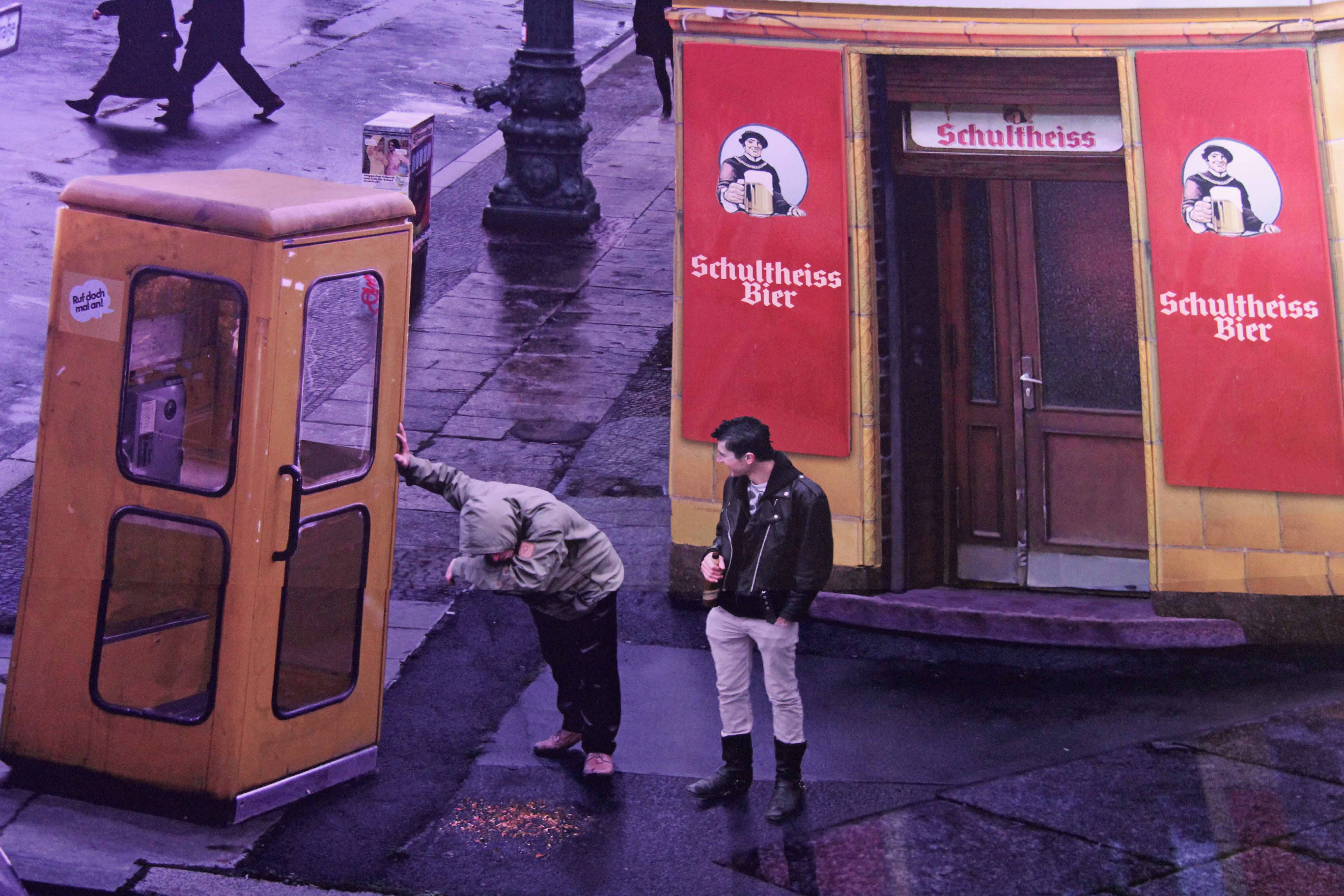A drinker is sick on the street in the Asisi Panorama: Die Mauer (The Wall) and exhibit near Checkpoint Charlie in Berlin