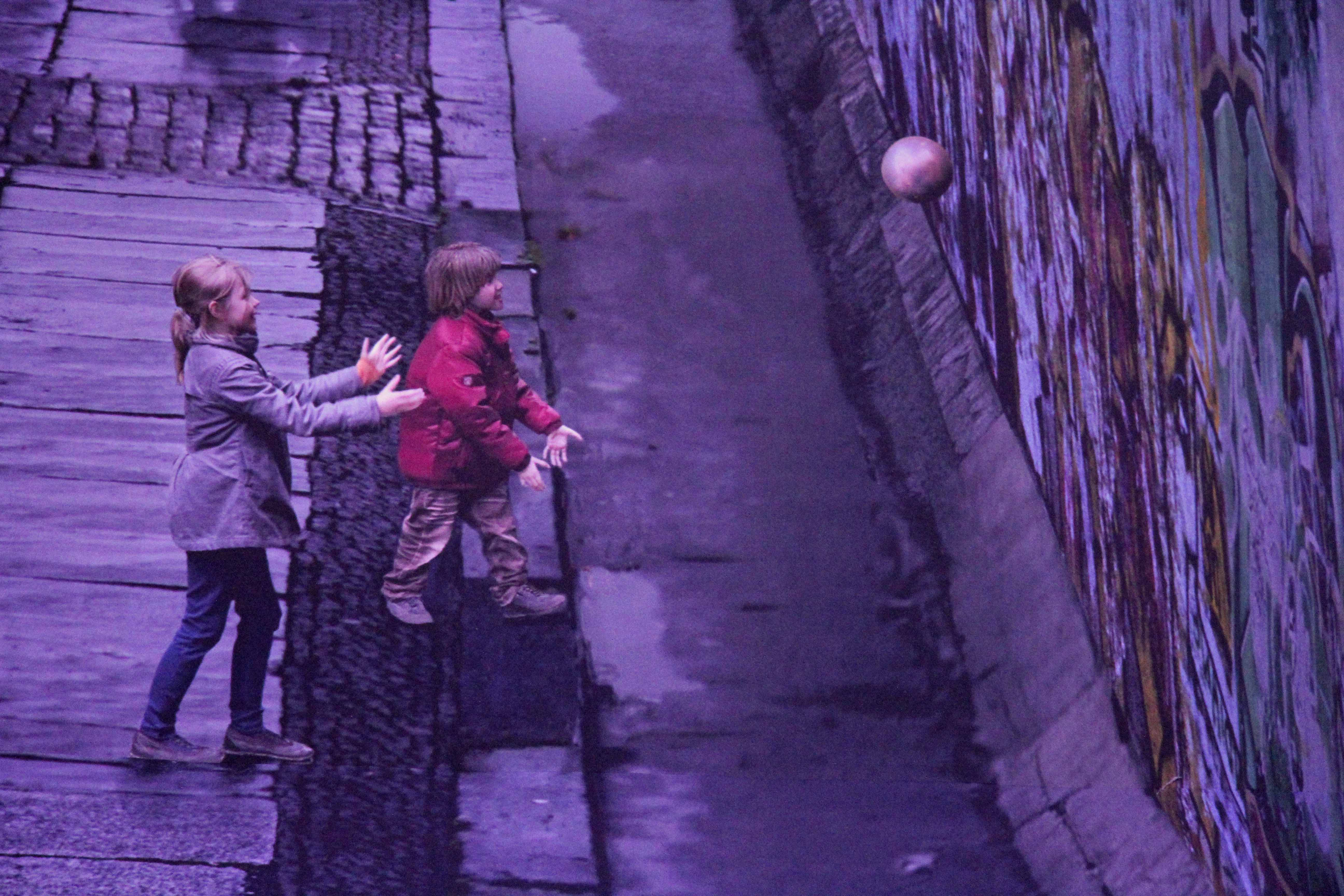 Children play a ball game up against the Wall in the Asisi Panorama: Die Mauer (The Wall) and exhibit near Checkpoint Charlie in Berlin