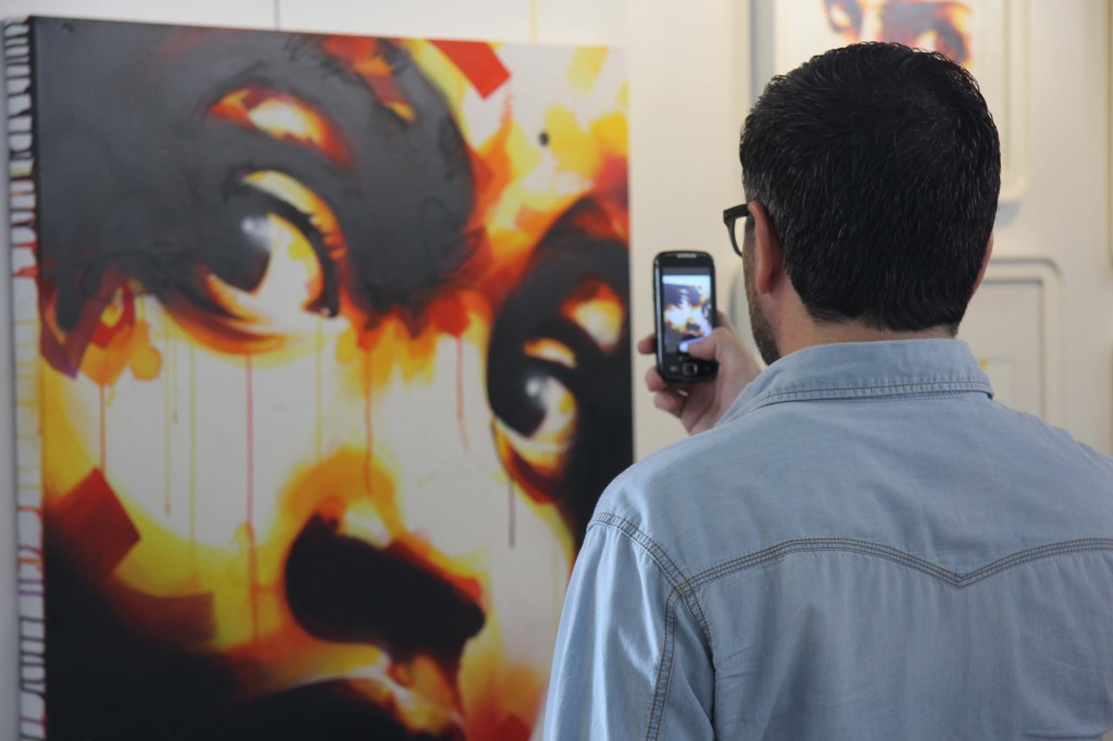 An appreciative visitor takes a picture of Dan 23 - Music Is The Key at Stroke Urban Art Fair 2012 in Berlin
