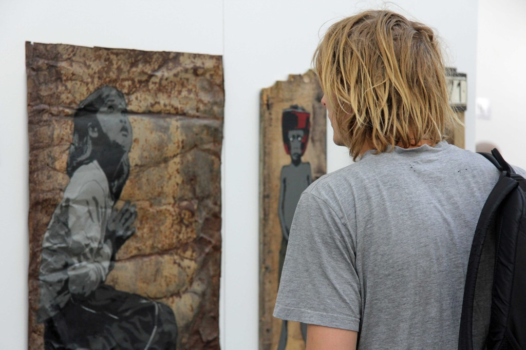 A visitor checks out the work by ALIAS at Stroke Urban Art Fair 2012 in Berlin