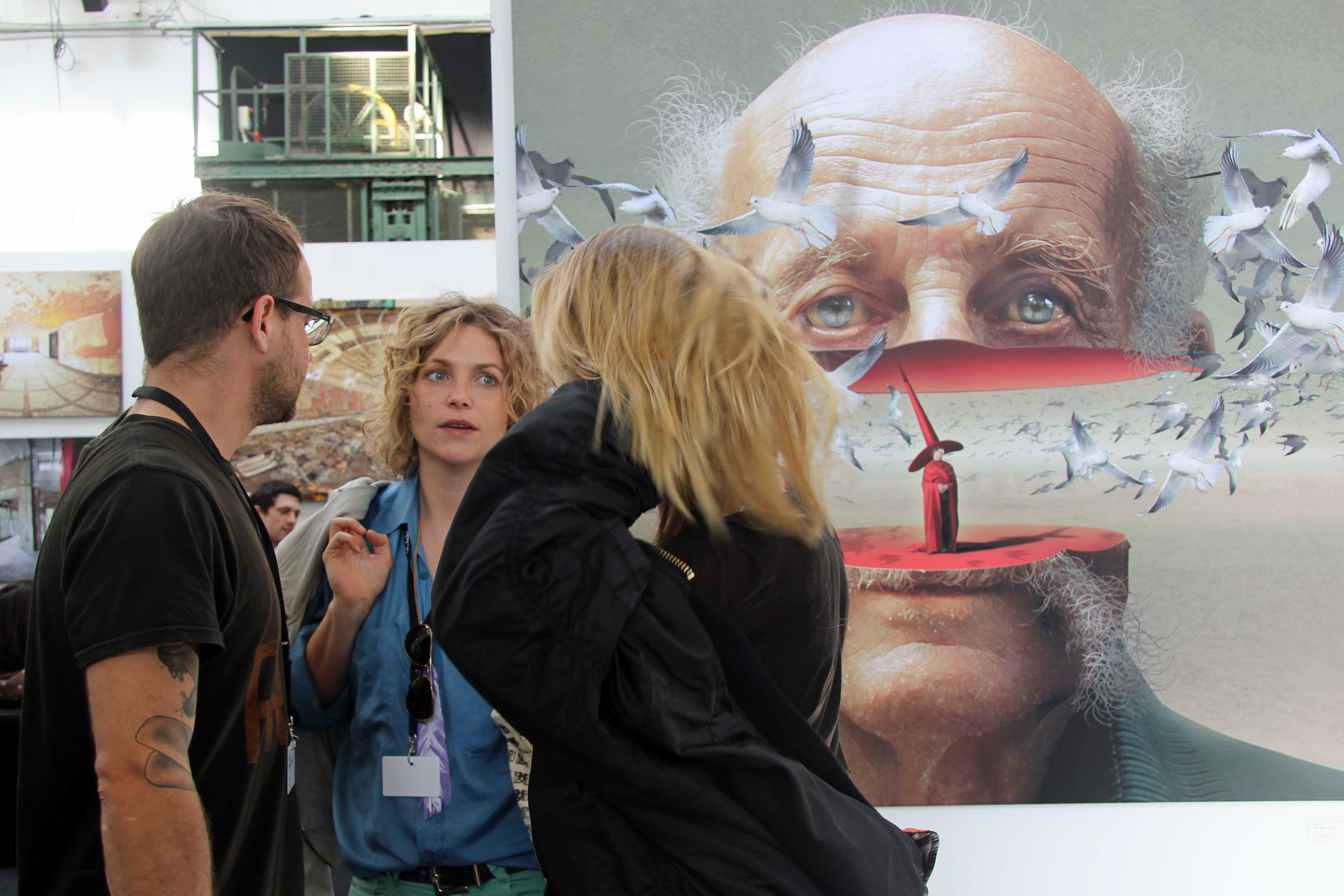 A group of visitors discuss the artwork at Stroke Urban Art Fair 2012 in Berlin