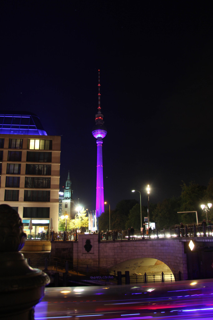 Fernsehturm (TV Tower) and in the foreground a boat streaks past on the Spree during the Berlin Festival of Lights