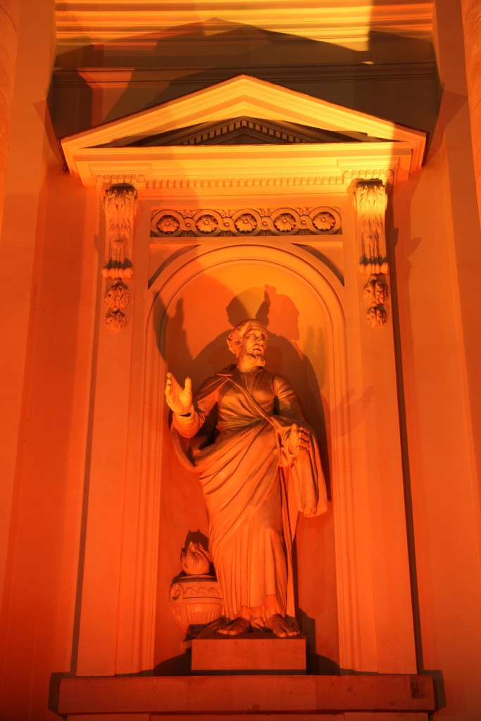 A statue on the Französischer Dom (French Cathedral) lit orange during the Berlin Festival of Lights