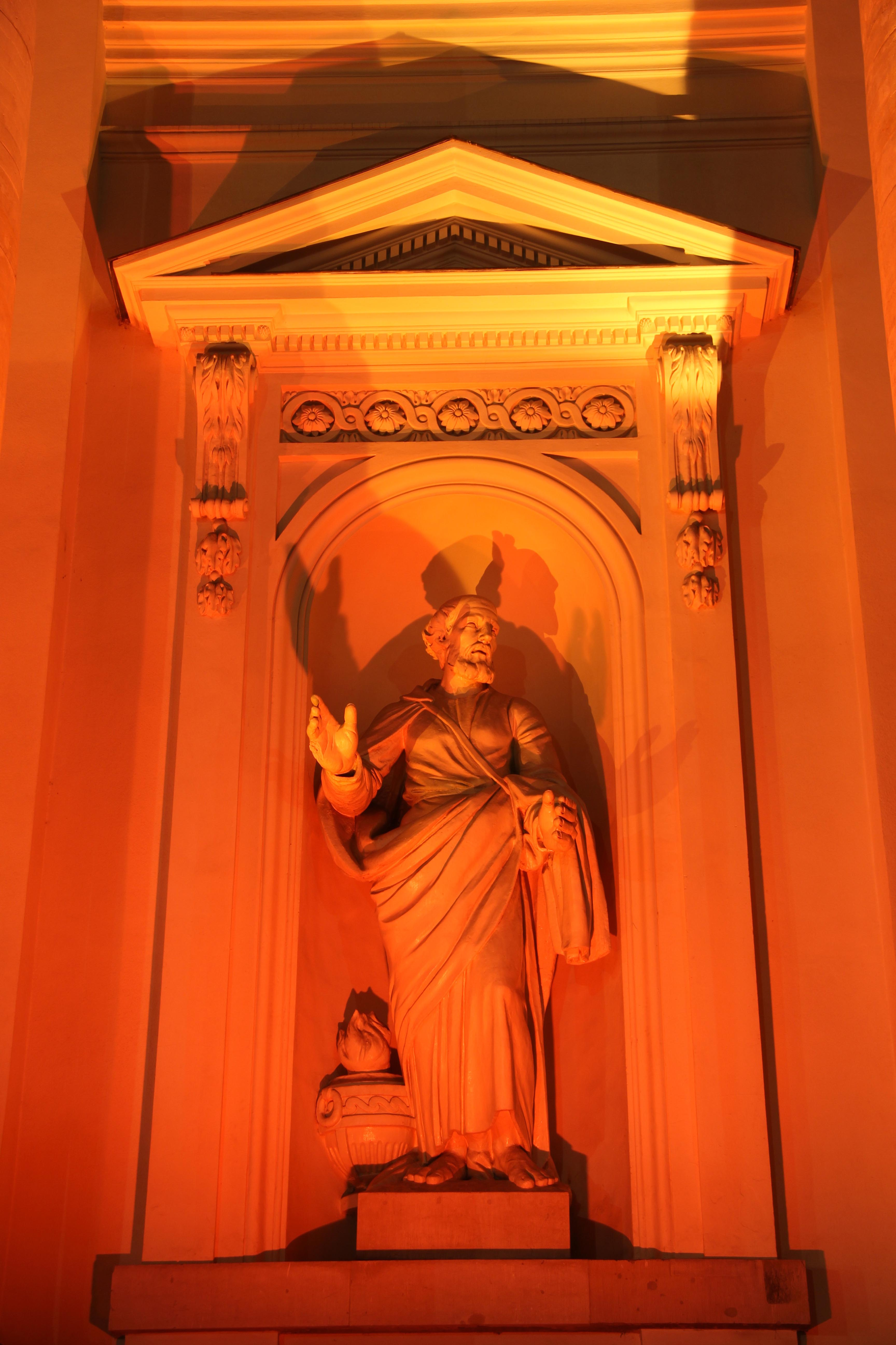 A statue on the Französischer Dom (French Cathedral) lit orange during the Festival of Lights in Berlin