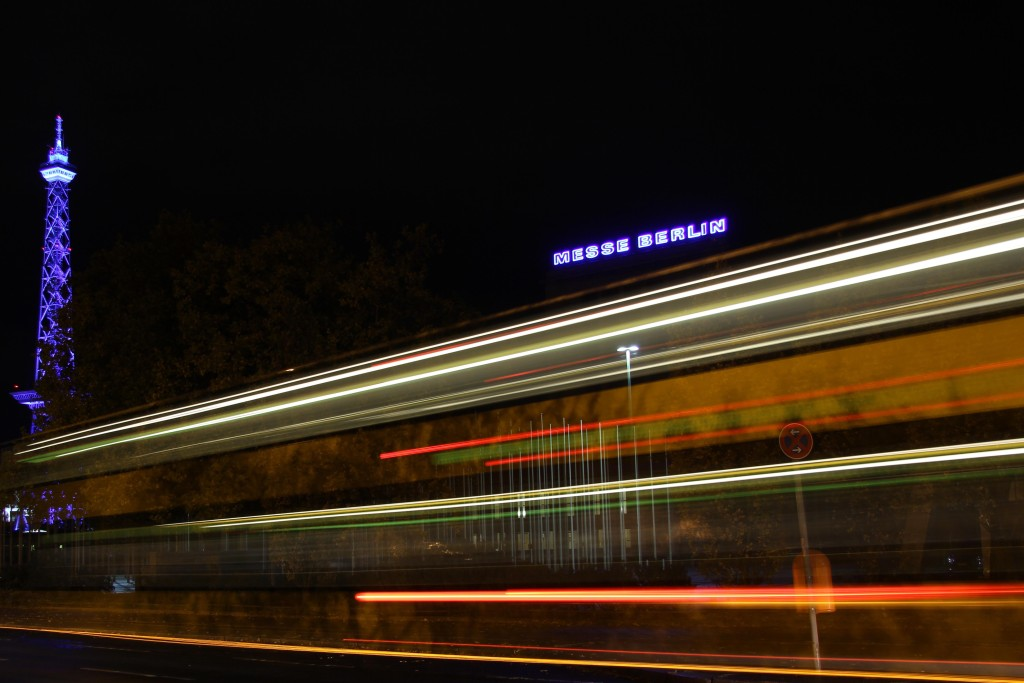 A bus streaks past the Funkturm (West Berlin TV Tower) and Messe Berlin lit up during the Berlin Festival of Lights