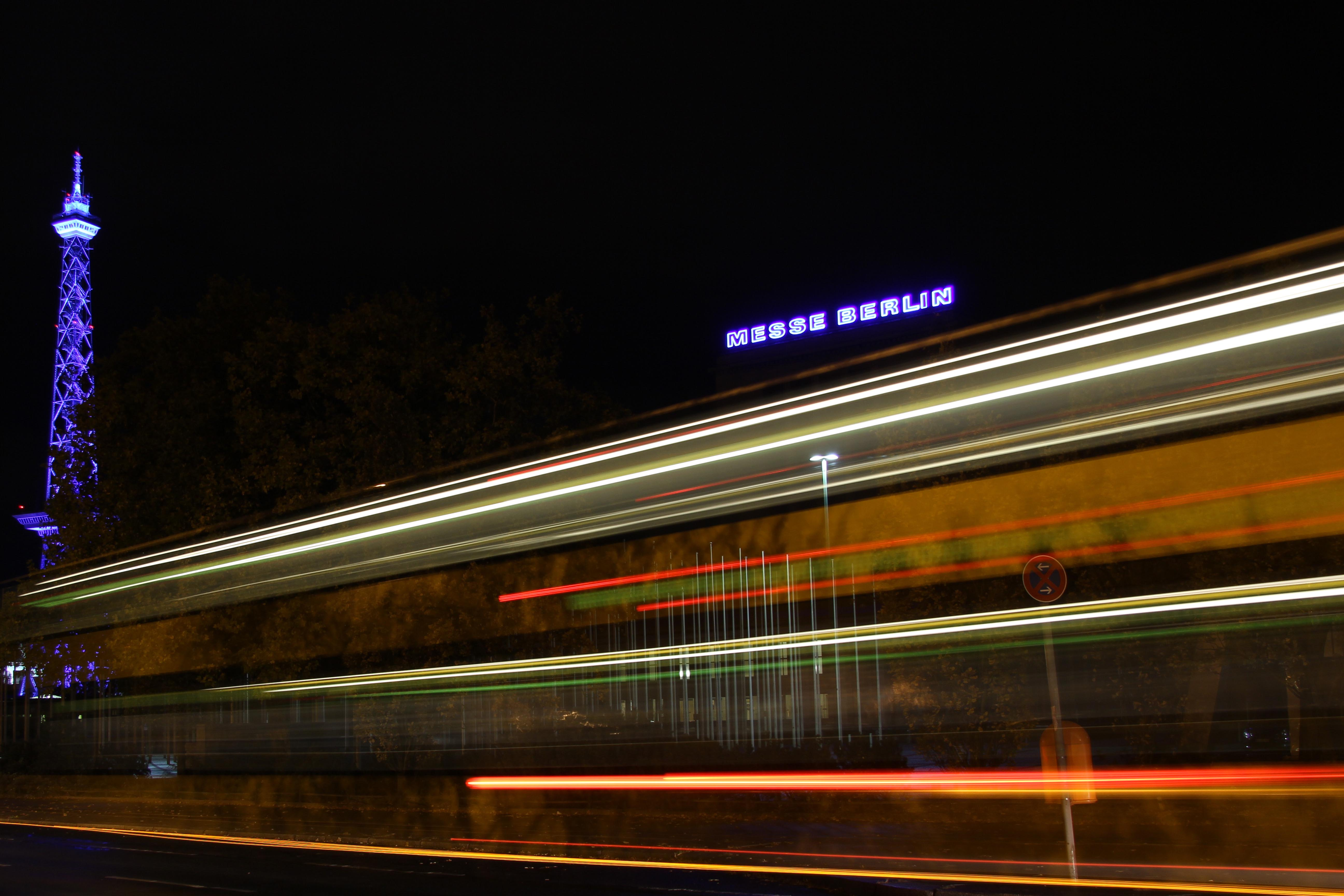 A bus streaks past the Funkturm (West Berlin TV Tower) and Messe Berlin lit up during the Festival of Lights in Berlin