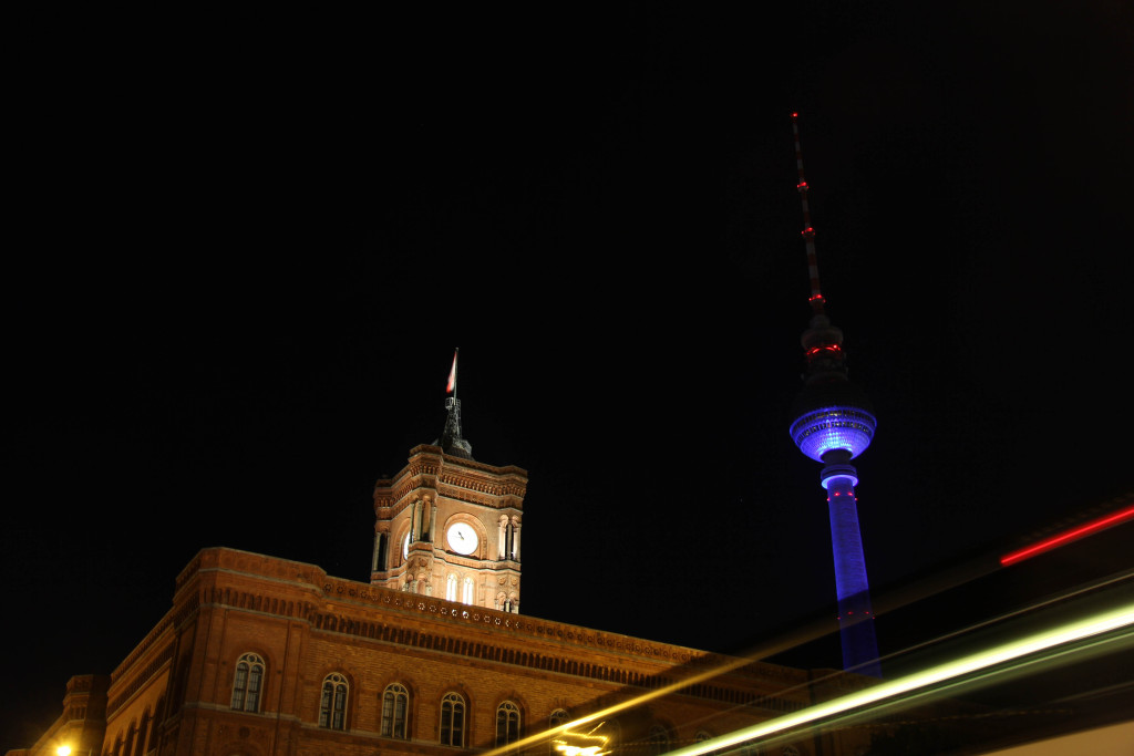 A bus streak past the Rotes Rathaus (Red City Hall) and the Fernsehturm (TV Tower) lit up during the Berlin Festival of Lights