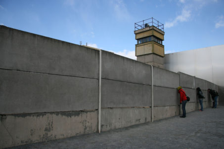 Tourists peer through gaps in the Berlin Wall at a Watchtower at Gedenkstätte Berliner Mauer