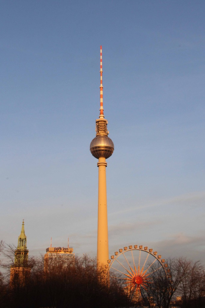 The Fernsehturm and a Ferris Wheel set up for the Christmas Market at sunset from the Schlossplatz in Berlin