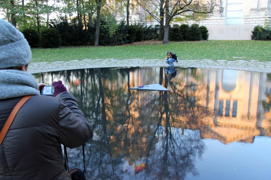 A lady takes a photograph of the Memorial to the Sinti and Roma of Europe Murdered Under National Socialism in Berlin