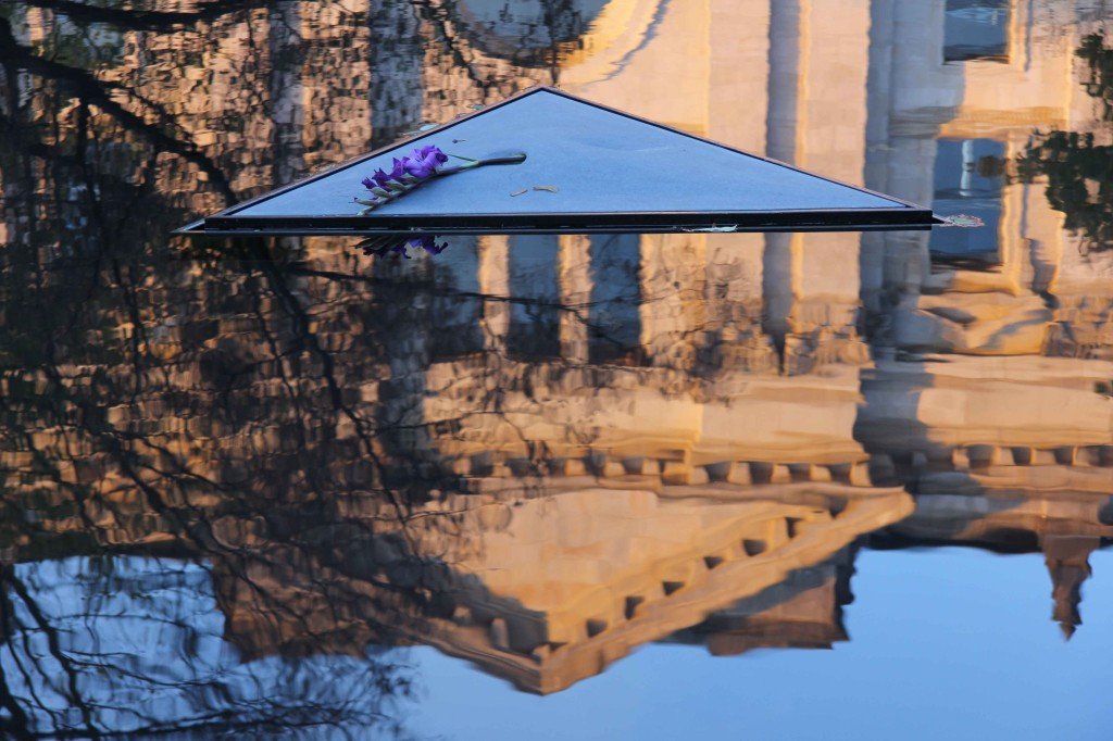 The reflection of the Reichstag in the water of the Memorial to the Sinti and Roma of Europe Murdered Under National Socialism in Berlin