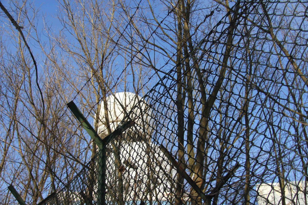 A dome of the former NSA Listening Station at Teufelsberg in Berlin seen through the perimeter fence