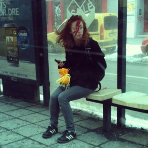 A girl with Bowie face paint at a tram stop in Berlin
