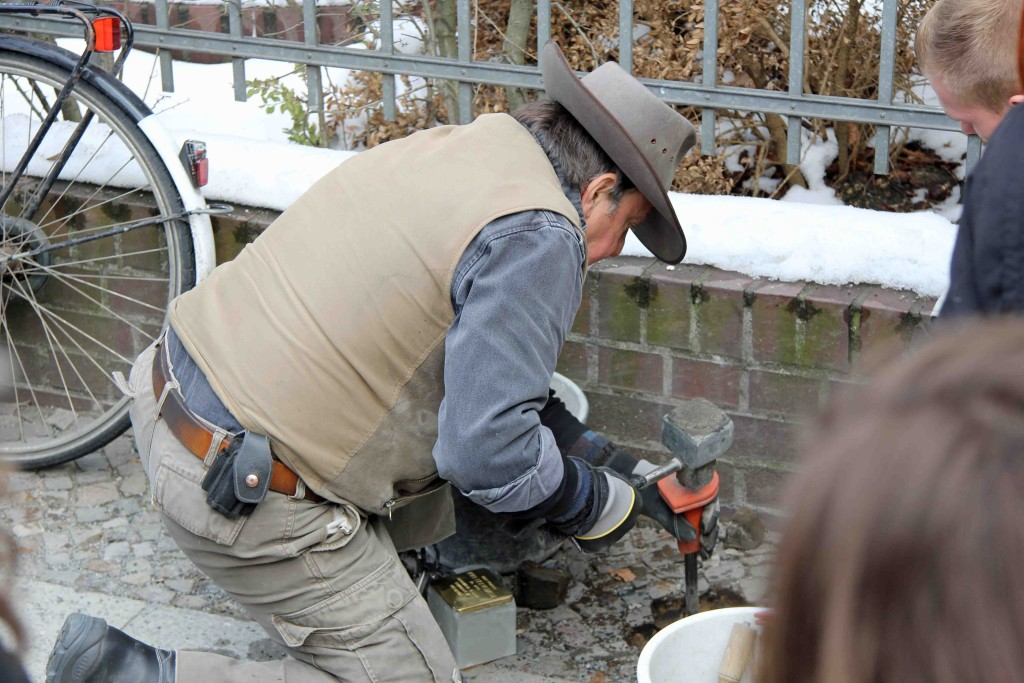 Gunter Demnig digging a hole to lay Stolpersteine in memory of the Eisenstädt family outside Erkelenzdamm 9 in Berlin Kreuzberg