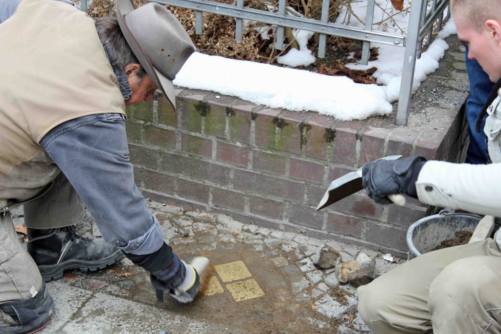 Gunter Demnig sweeps a newly laid group of Stolpersteine in memory of the Eisenstädt family outside Erkelenzdamm 9 in Berlin Kreuzberg