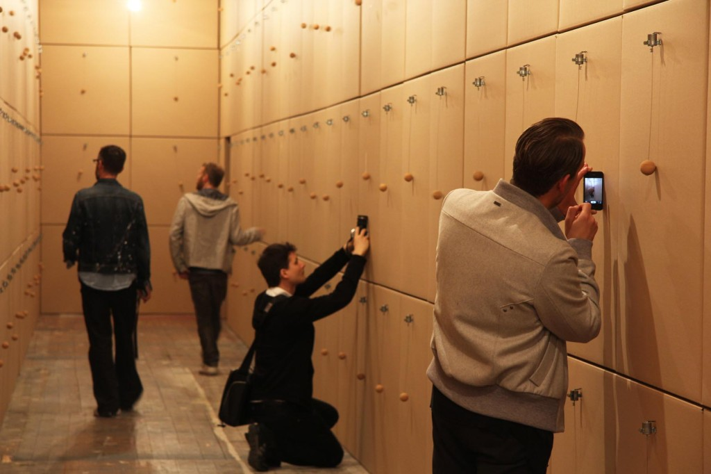 Visitors taking photos of the installation by Zimoun – Prepared dc-motors, cork balls, cardboard boxes at the Olympus OM-D Photography Playground the Opernwerstätten in Berlin