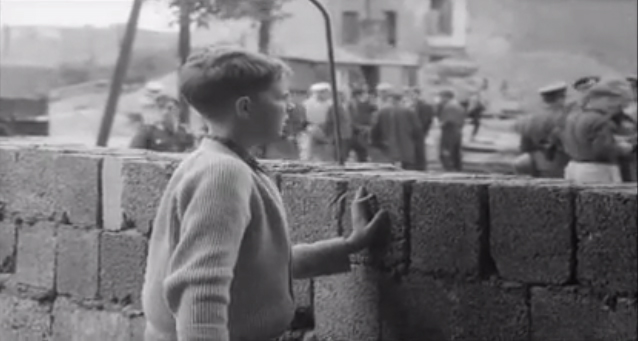 A boy stands at the Berlin Wall in 1961