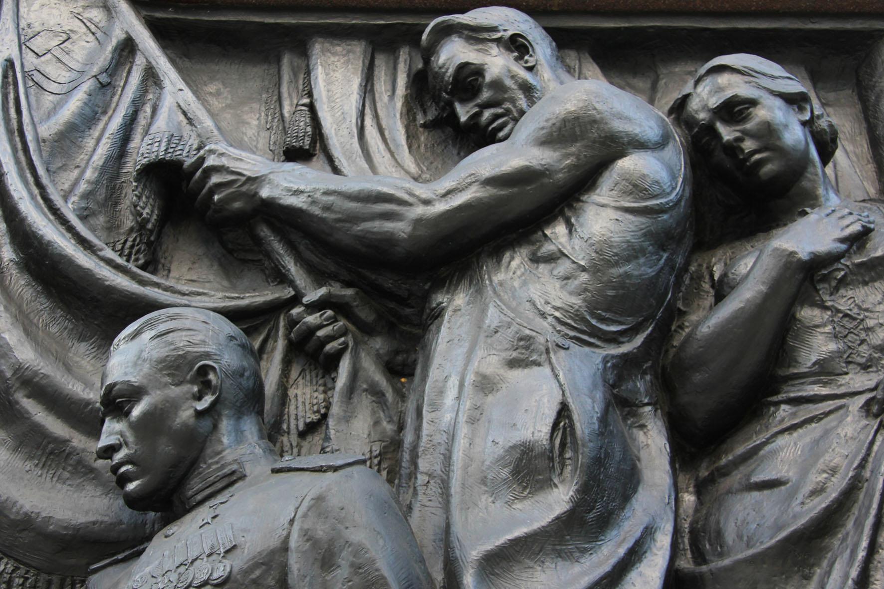 Ein Bronze Relief von Soldaten und trauernden Eltern an dem Sowjetischen Ehrenmal Schönholzer Heide in Berlin