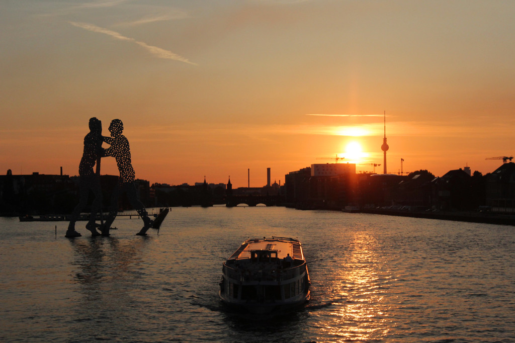 Sunset from Elsenbrücke Berlin with a view of the Molecule Man, Oberbaumbrücke and Fernsehturm and a boat on the River Spree
