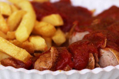 Eine Nahaufnahme von der Currywurst mit Pommes von Schmidts Imbiss in Berlin - einer der besten Currywurst in Berlin