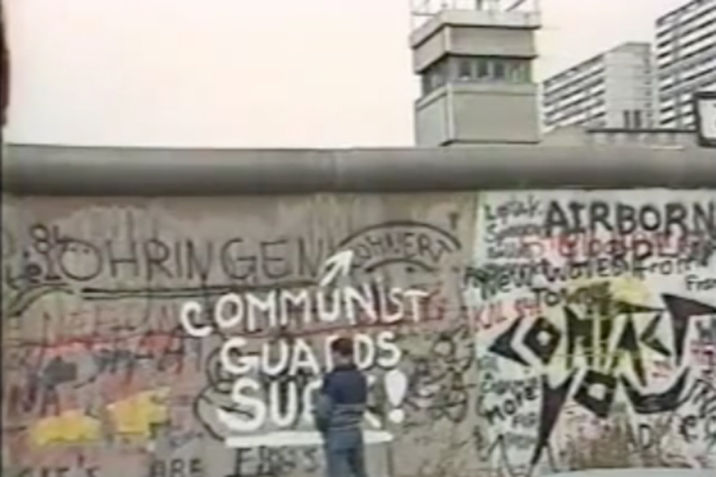 A man takes a leak against the Berlin Wall near Checkpoint Charlie - 'Berlin Wall 1984' by AZCelts on YouTube