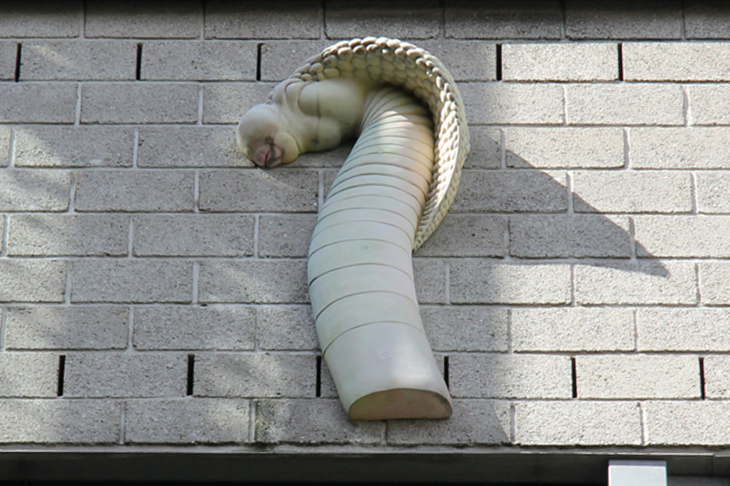 Der Schlangenkopf auf dem Riesen Penis Relief (eine Kai Diekmann-Karikatur) - Friede sei mit Dir oder der Pimmel über Berlin von Peter Lenk - auf dem Bürogebäude der Tageszeitung (Taz) auf der Rudi-Dutschke-Straße in Berlin