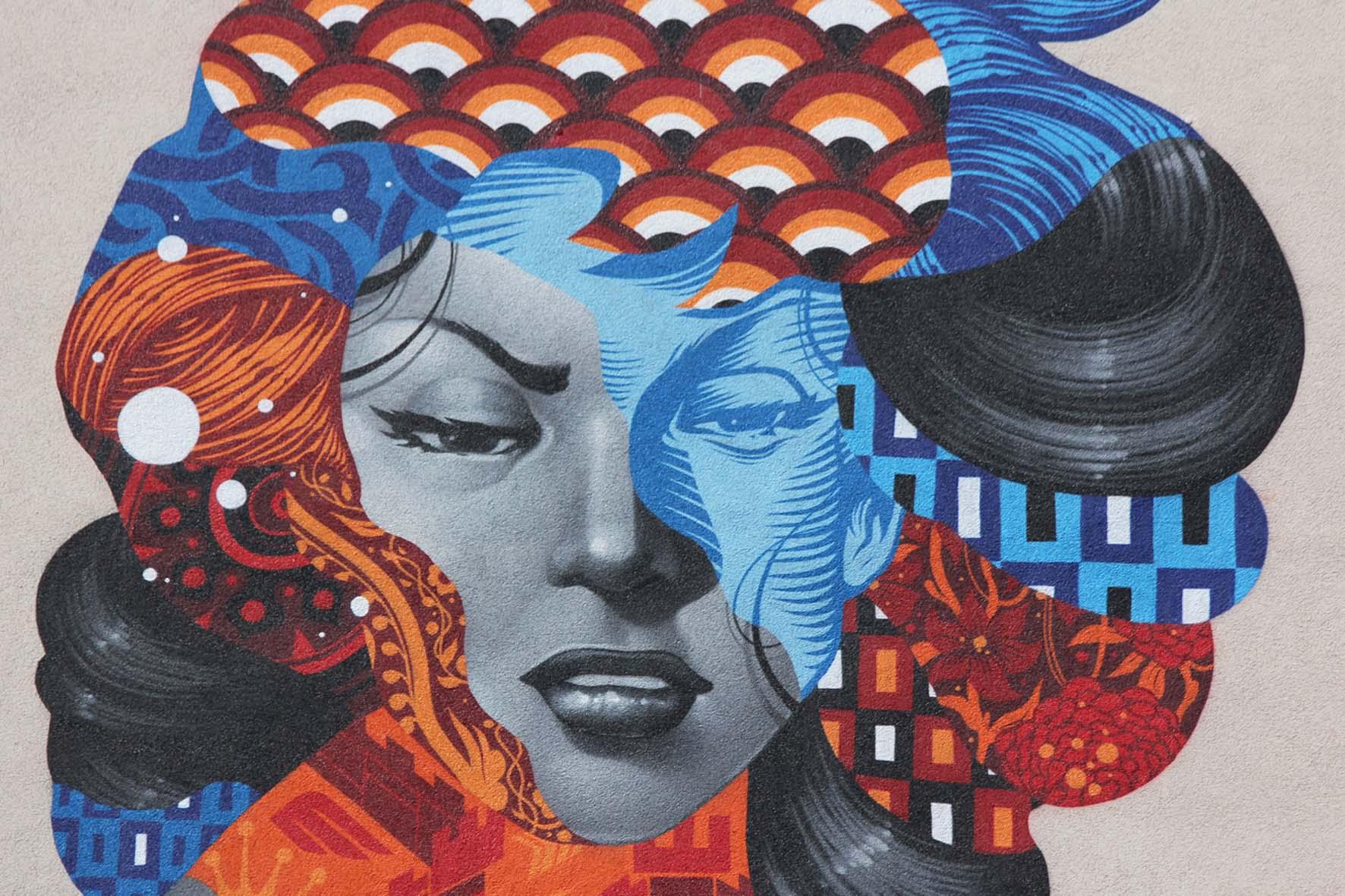 Eine Nahaufnahme des Gesichts des Street Art Murals Attack of the 50 Foot Socialite von Tristan Eaton am Am Friedrichshain 33 in Berlin
